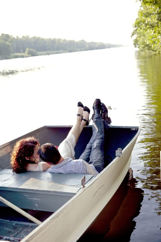 Couple relaxing in a rowboat during an engagement photo shoot