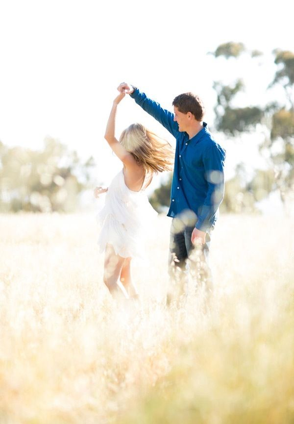Couple dancing in a field for their engagement photo shoot